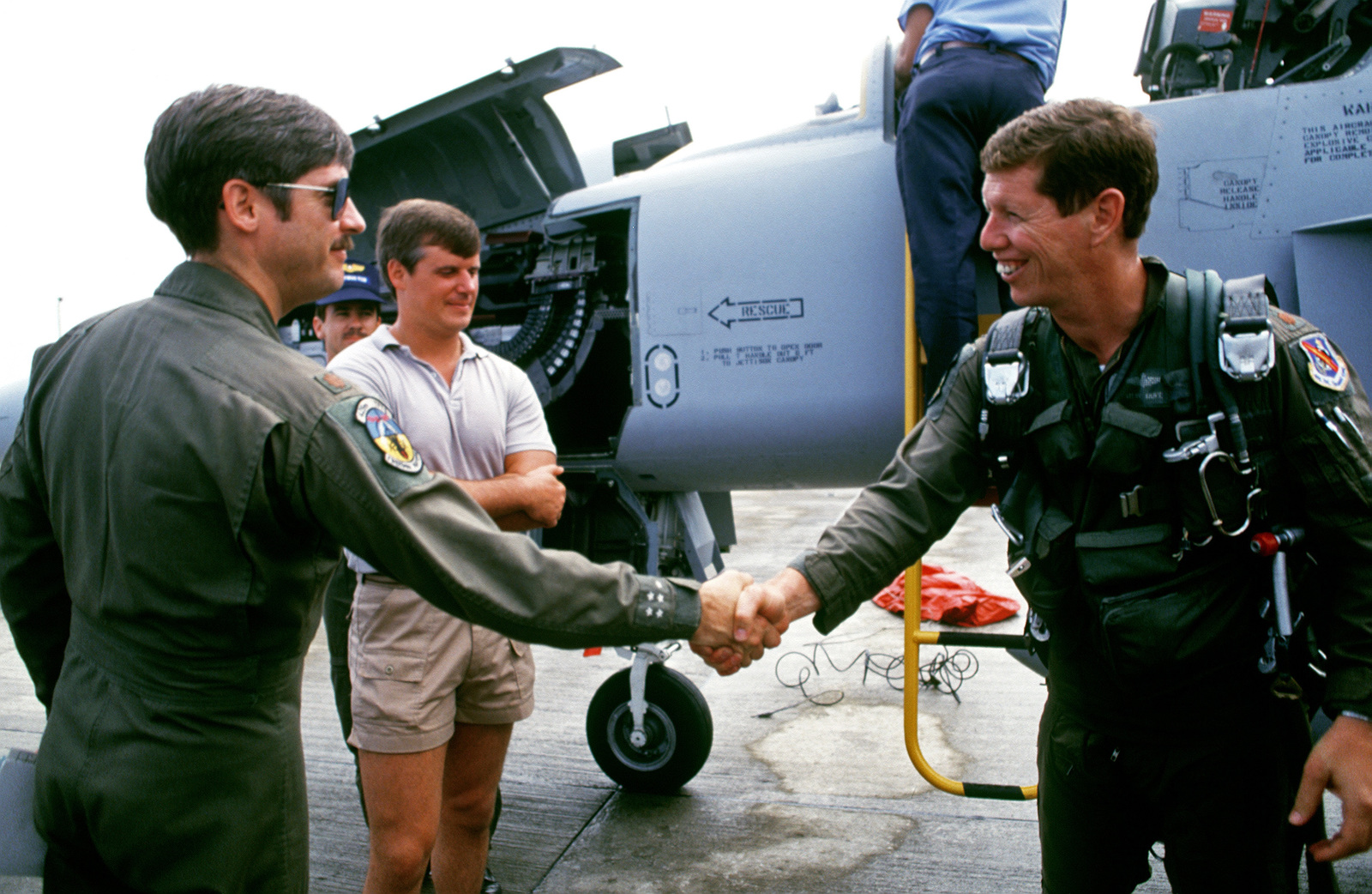 Two pilots from the 425th Tactical Fighter Training Squadron (425th TFTS) shake hands after the arrival of the pilot at right.  Behind them, civilian technicans work on an F-5E Tiger II aircraft. Thirty members of the 425th TFTS are in Honduras to support Exercise AMIGO SOUTH and to cross train with the Honduran air force.